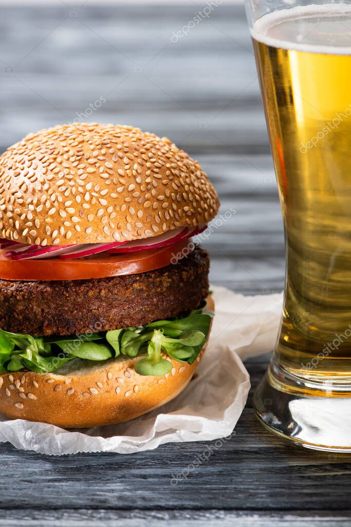 Tasty vegan burger with microgreens, radish and tomato served on wooden table with beer stock vector