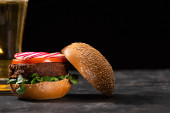 selektivní zaměření chutného veganského burgeru s mikrozelení, ředkvičkami a rajčaty podávané na texturovaném povrchu s pivem izolovaným na černém