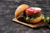 chutný veganský burger se zeleninou podávaný na dřevěné řezací desce na texturovaném povrchu