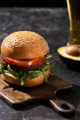selektivní zaměření chutného veganského burgeru s rajčaty a zeleninou podávané na dřevěné desce na texturovaném povrchu s pivem a avokádem
