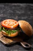 selektivní zaměření chutného veganského burgeru s rajčaty a zeleninou podávané na dřevěné desce na texturovaném povrchu