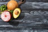 vrchní pohled na chutný veganský burger s mikrozelení, ředkvičkami, rajčaty a avokádem na řezací desce servírované na dřevěném stole