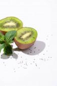 chutné kiwi ovoce v blízkosti čerstvé máty peprné a černá semena na bílém