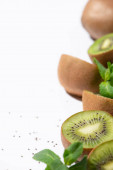 selective focus of green kiwi fruits near organic peppermint and black seeds on white