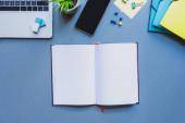 Top kilátás nyílt notebook közelében digitális eszközök és irodai kellékek kék felületen