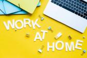 Top kilátás a munka otthon felirat közelében laptop és írószer sárga háttér