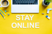 Top view of stay online lettering near laptop, coffee and stationery on yellow background