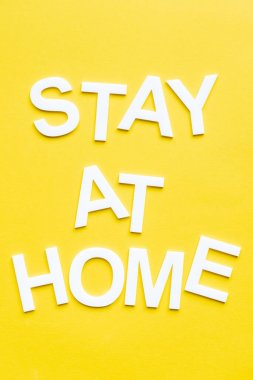 Top view of stay at home white lettering on yellow background stock vector