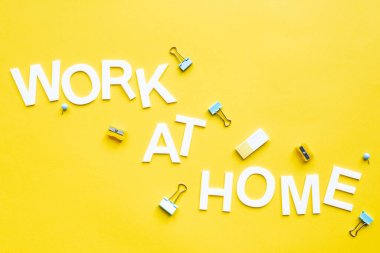 Top view of work at home lettering with pencil sharpeners, binder clips and eraser on yellow surface stock vector
