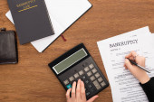 partial view of woman filling in bankruptcy form and using calculator on wooden background