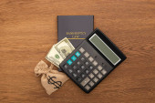 top view of bankruptcy law book, cash and money bag, calculator on wooden background