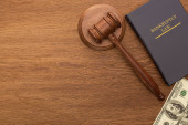 top view of money, bankruptcy law book and gavel on wooden background