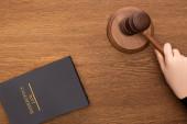 abgeschnittene Ansicht einer weiblichen Hand mit Hammer nahe Konkursrechtsbuch auf hölzernem Hintergrund
