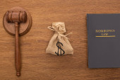 top view of bankruptcy law book, money bag and gavel on wooden background