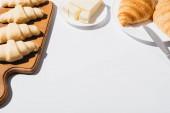 čerstvé pečené a syrové croissanty s máslem na bílém pozadí