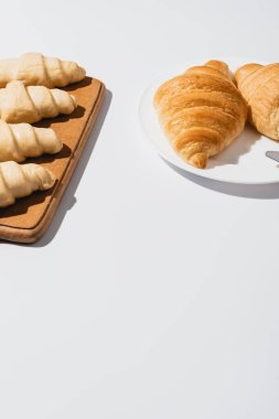 Fresh baked and raw croissants on white background stock vector