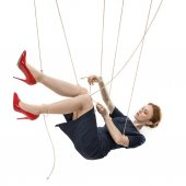 businesswoman hanging on manipulating ropes