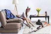 Fotografie junge Sportlerin, warme Socken, Ski-Ausrüstung am Boden liegend
