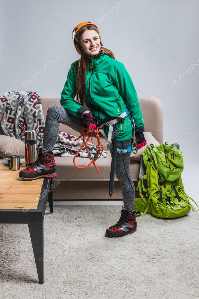 beautiful smiling climber in helmet with climbing equipment at home