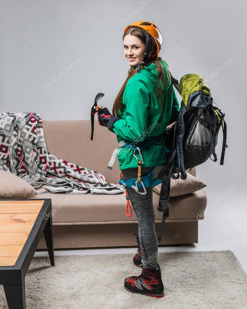 beautiful climber in helmet with climbing equipment at home