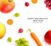Tvůrčí šťastný a zdravý novoroční přání z ovoce na bílém pozadí. Ovoce šťastný nový rok, pohled shora, slavnostní přání.