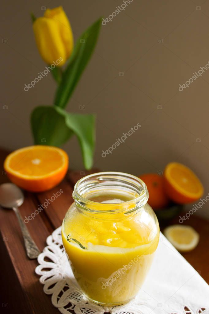 Orange-lemon curd and slices of oranges and lemons on a wooden surface. Rustic style.