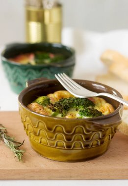 Baked scrambled eggs with broccoli, sausages and cheese served with slices of bread. Rustic style.