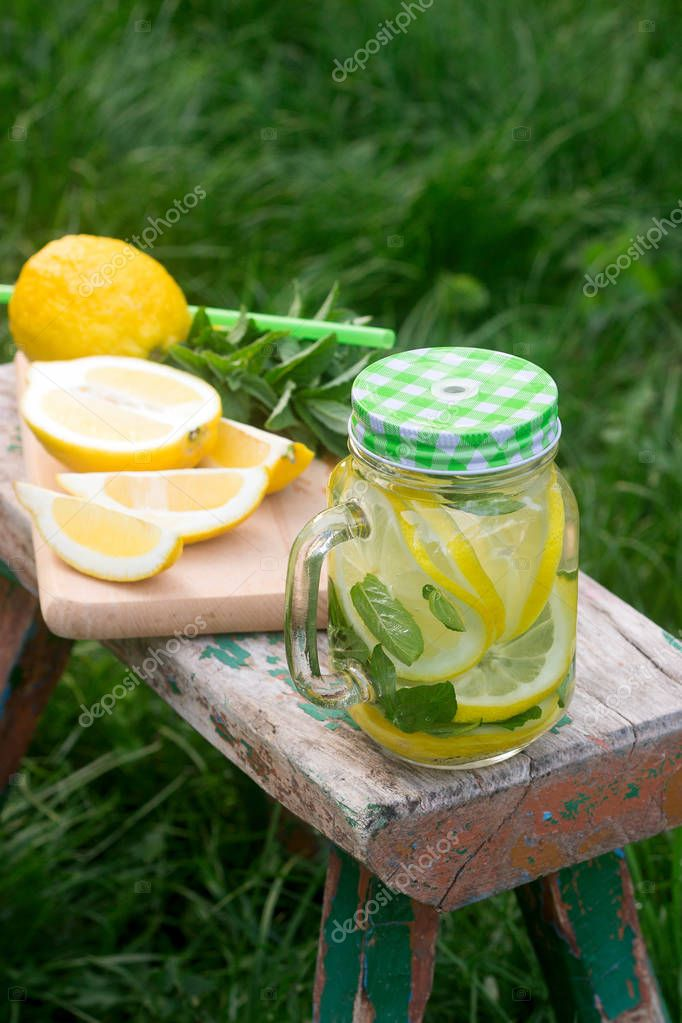 Homemade lemonade with mint and ice on a wooden bench in the garden. Rustic style.