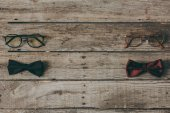 Photo stylish bow ties and eyeglasses on tabletop