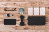smartphone s kolekcí peněz a doplňky na stůl