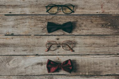 Row of stylish eyeglasses and bow ties on wooden tabletop stock vector