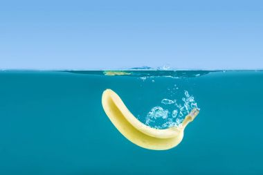 banana floating in water with bubbles