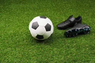Close-up of soccer ball with pair of black boots on grass stock vector