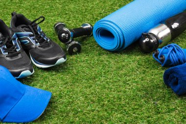 fitness equipment and cap on green pitch