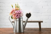 Beautiful flowers in watering can