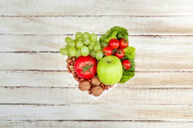 Top view of fresh organic vegetables and fruits on heart shaped plate, healthy eating concept stock vector