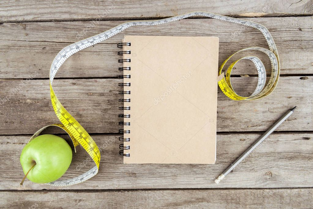 notebook, fresh apple and measuring tape