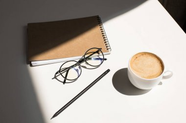 coffee, eyeglasses and notepad
