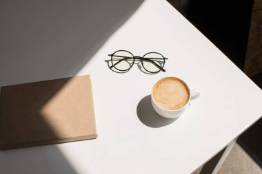 cup of coffee, eyeglasses and notepad