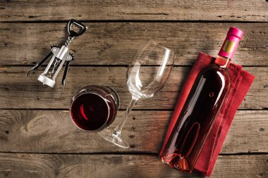 Top view of bottle of pink wine on napkin, corkscrew and two wineglasses on wooden tabletop stock vector