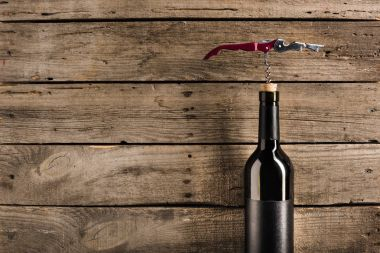 Top view of bottle of red wine and corkscrew on wooden tabletop with copy space stock vector