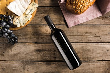 bottle of wine, bread and cheese