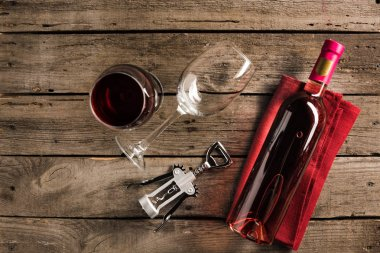 Top view of bottle of pink wine on red napkin, corkscrew and wineglasses on wooden tabletop stock vector