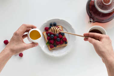 Cropped view of person with tea and toast with berries and honey for breakfast, isolated on white stock vector
