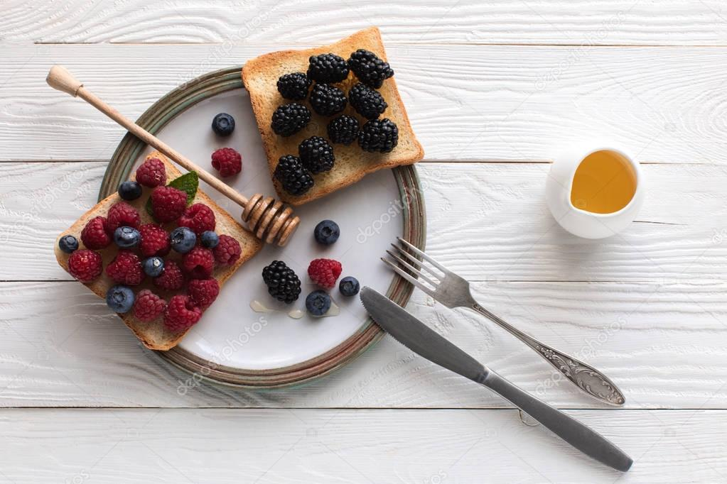 breakfast with berries on toasts and honey