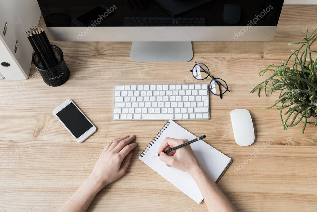 woman writing in notebook at workplace