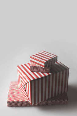 Stack of christmas gift boxes in red and white stripes, isolated on grey stock vector
