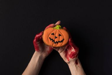 hands holding halloween cookie