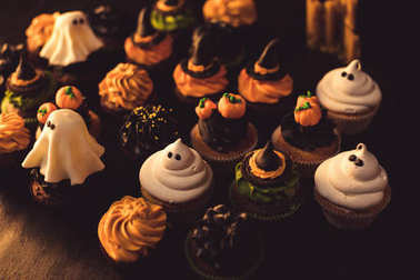 Close-up view of various tasty homemade halloween cupcakes stock vector