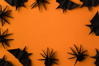 Halloween frame with black origami spiders and bats, isolated on orange stock vector